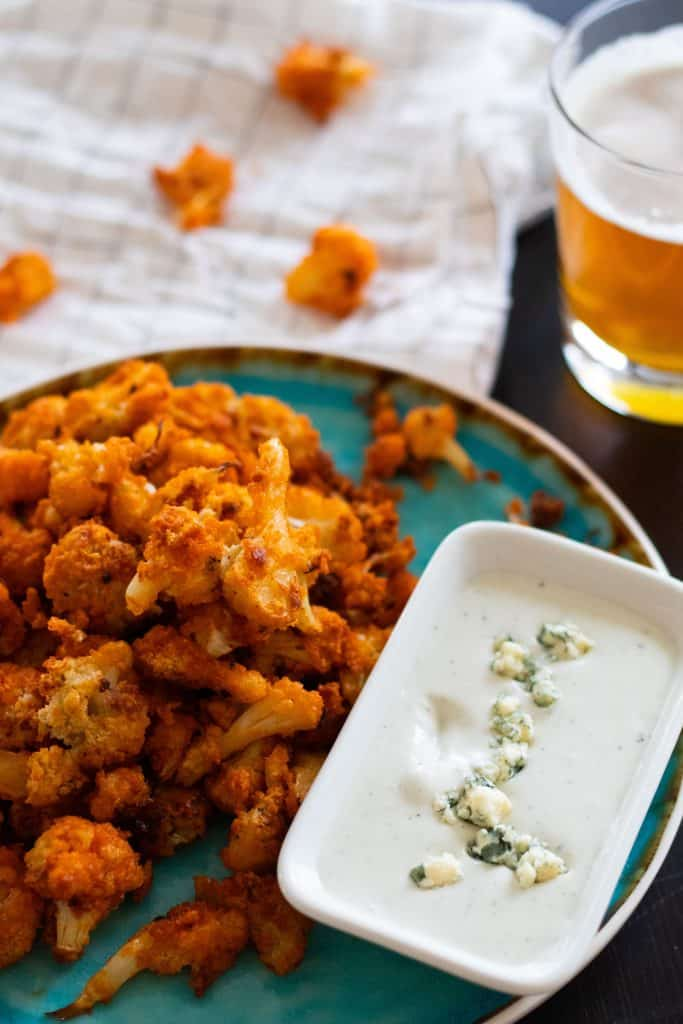 buffalo cauliflower bites and blue cheese suce next to a glass of beer