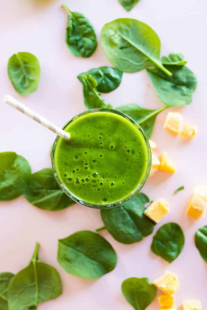 top view of green smoothie in a glass with a straw with mango pieces and spinach leaves around