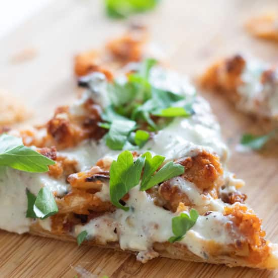 closeup of a slice of puff pastry pizza with buffalo cauliflower and blue cheese sauce