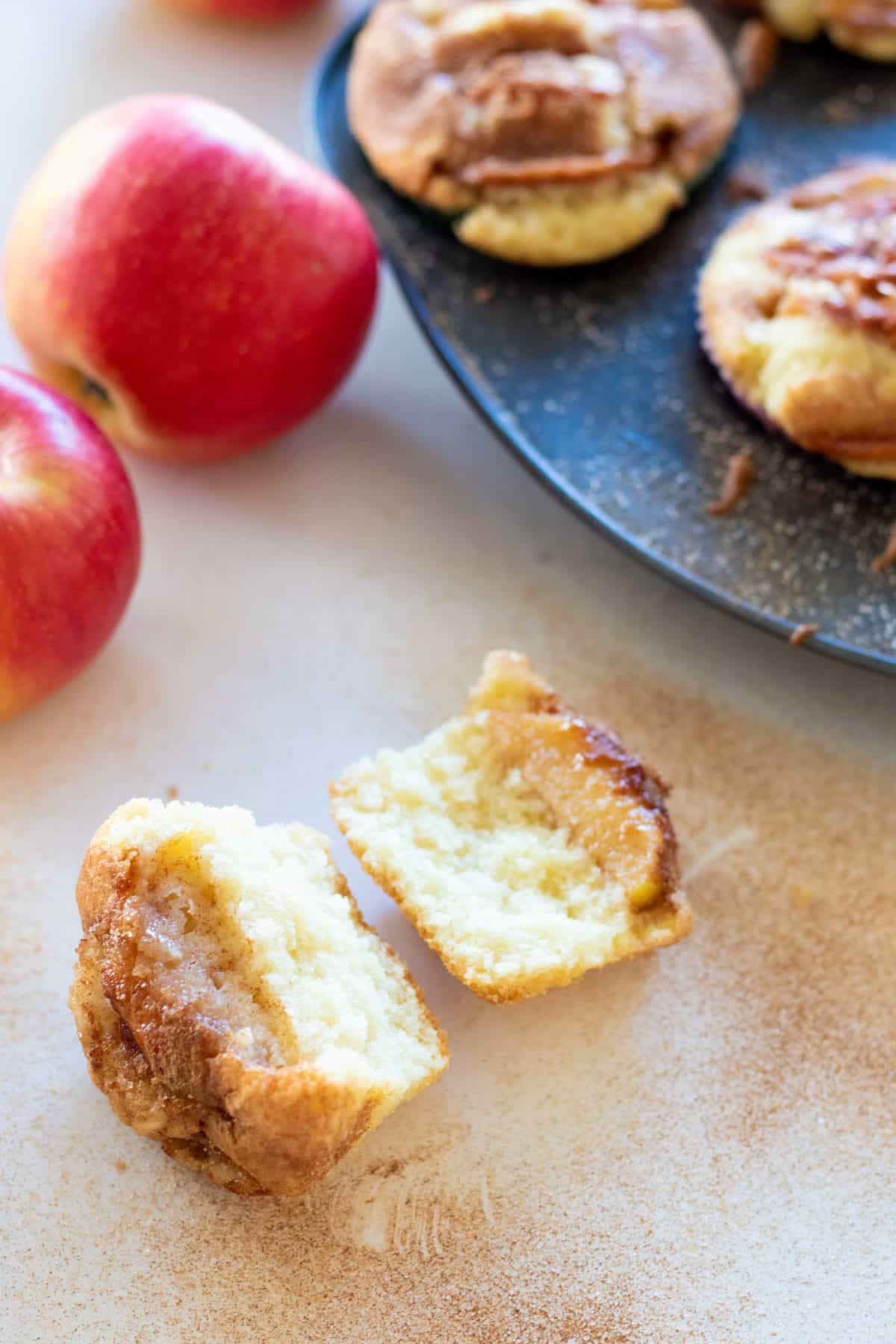 an apple muffin split in half in front of a muffin tin filled with muffins