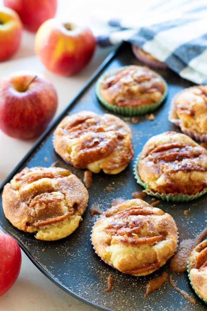 cinnamon apple muffins in a muffin tin with apples in the background