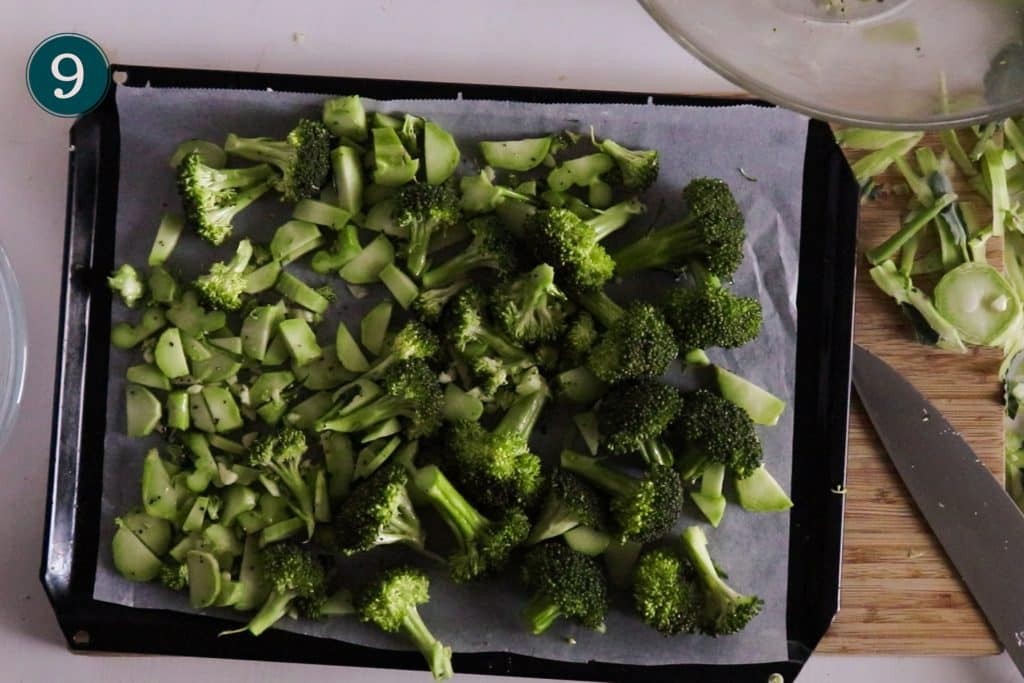 garlic roasted broccoli on an oven tray ready to be placed in the oven