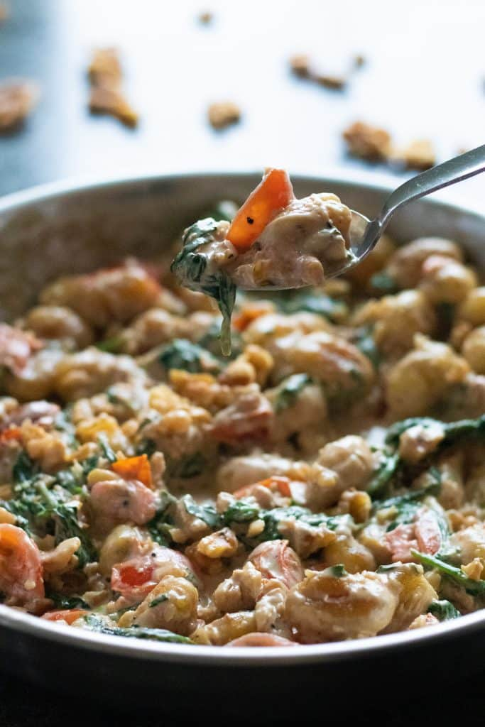 a spoonful of creamy gnocchi with gorgonzola picked up from a pan full of it