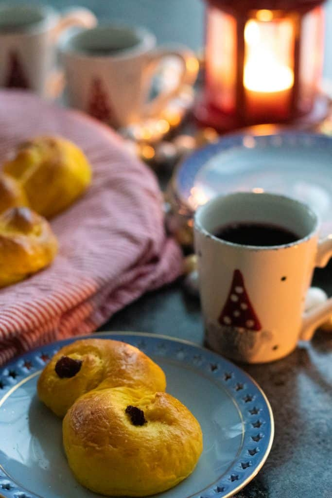 a Swedish saffron bun on a plate in front of a cup of glögg