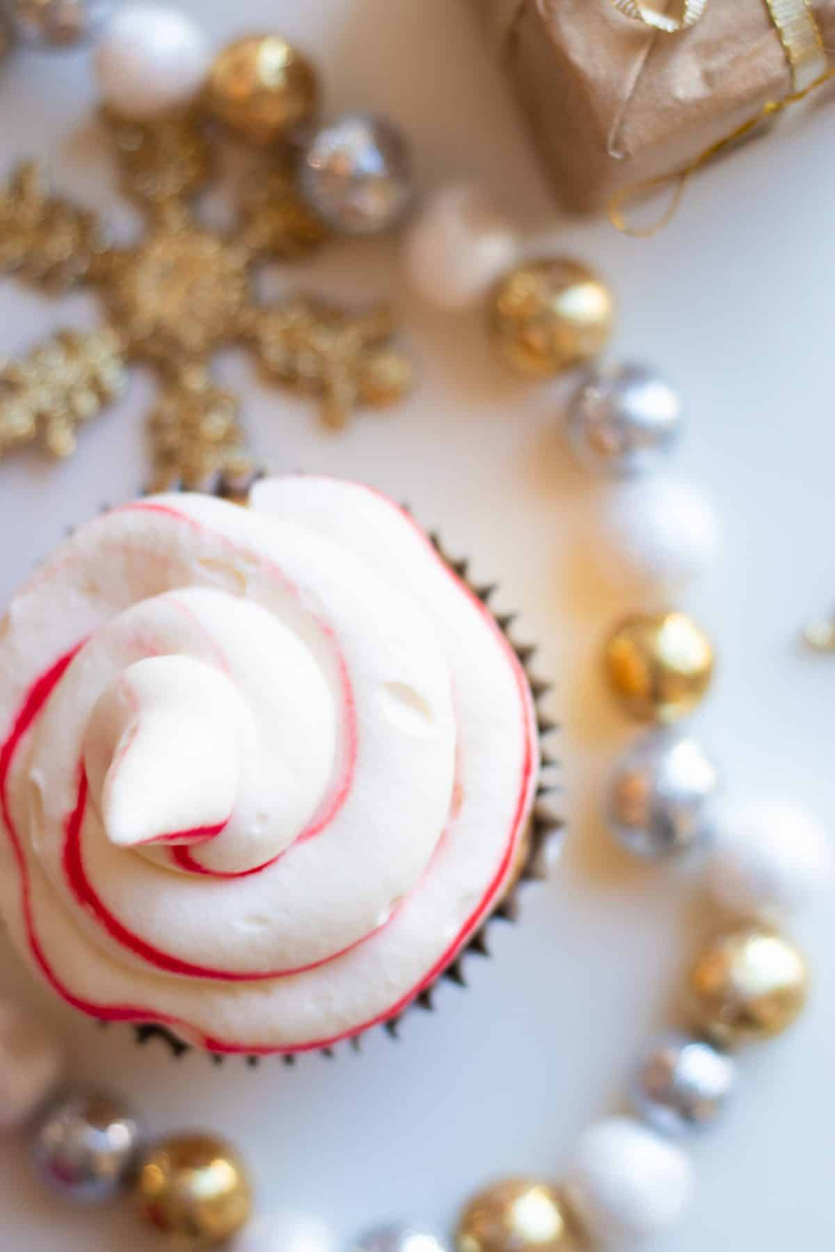 top down view of a candy cane cupcake with christmas decorations on the side