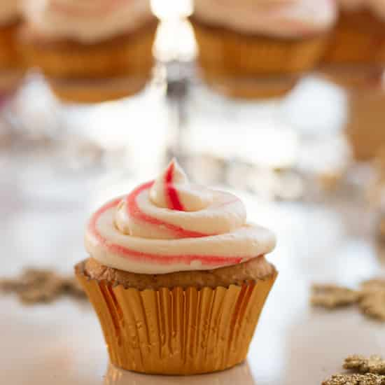 side view of a candy cane cupcake in front of a stand with cupcakes