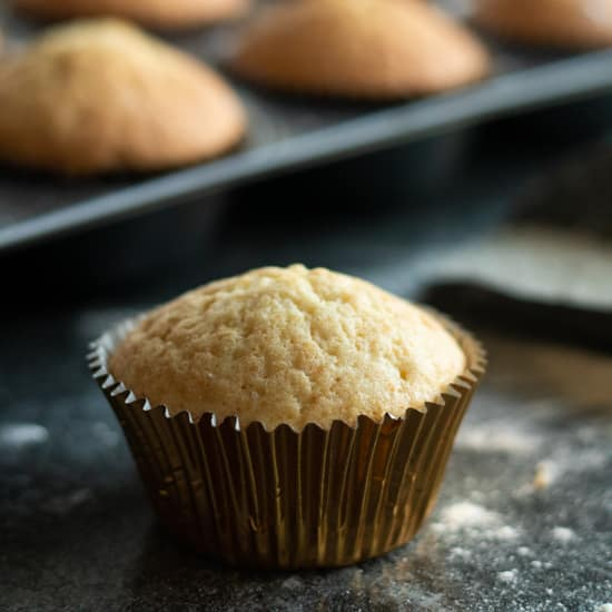 side view of a vanilla muffin in front of a tray of vanilla muffinsin