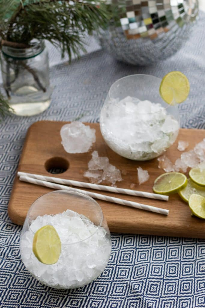 two glasses with crushed ice next to a wooden chopping board with paper straws and lime slices