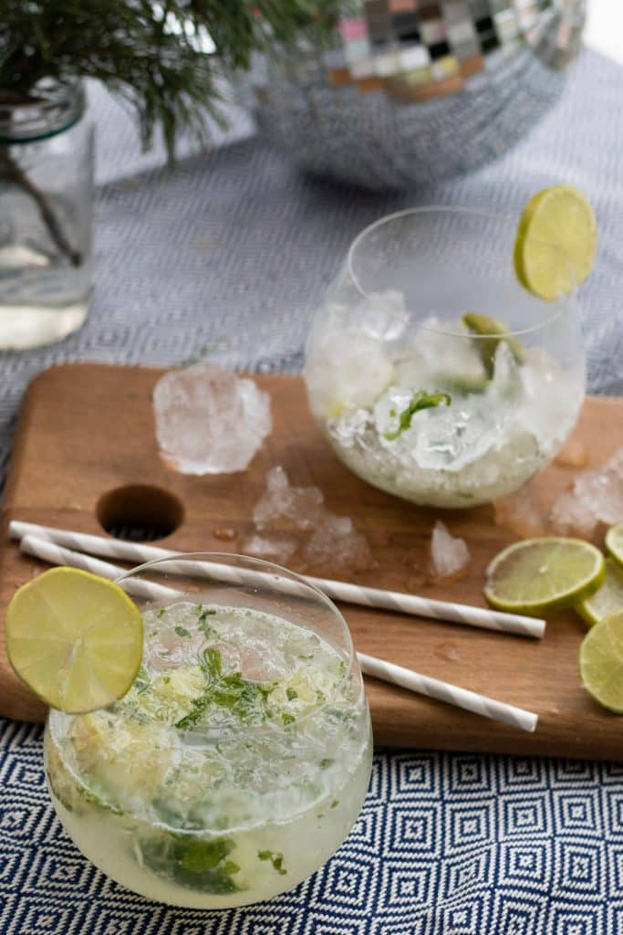 a mojito mocktail in a glass with a wooden chopping board with ice, paper straws and lime slices in the background