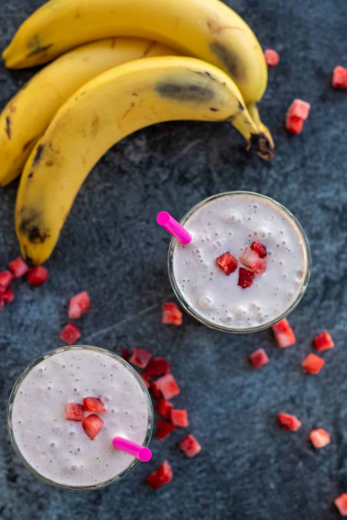 top down view of two strawberry banana smoothies with bananas and frozen starwberries around