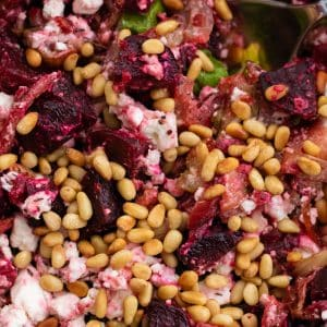 closeup of roast beetroot salad with feta cheese topped with pine nuts