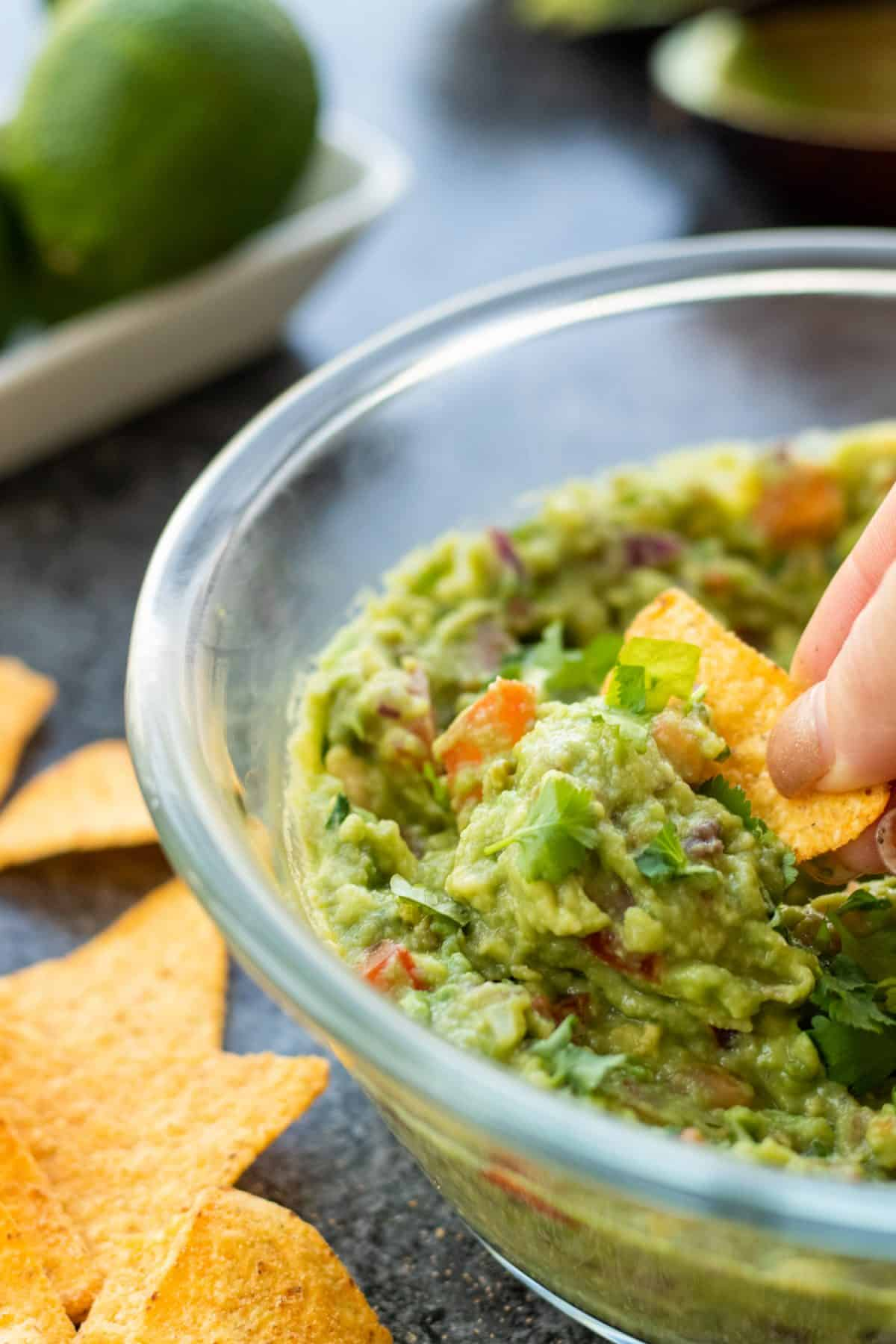 side view of a bowl of guacamole with a chip being dipped into it