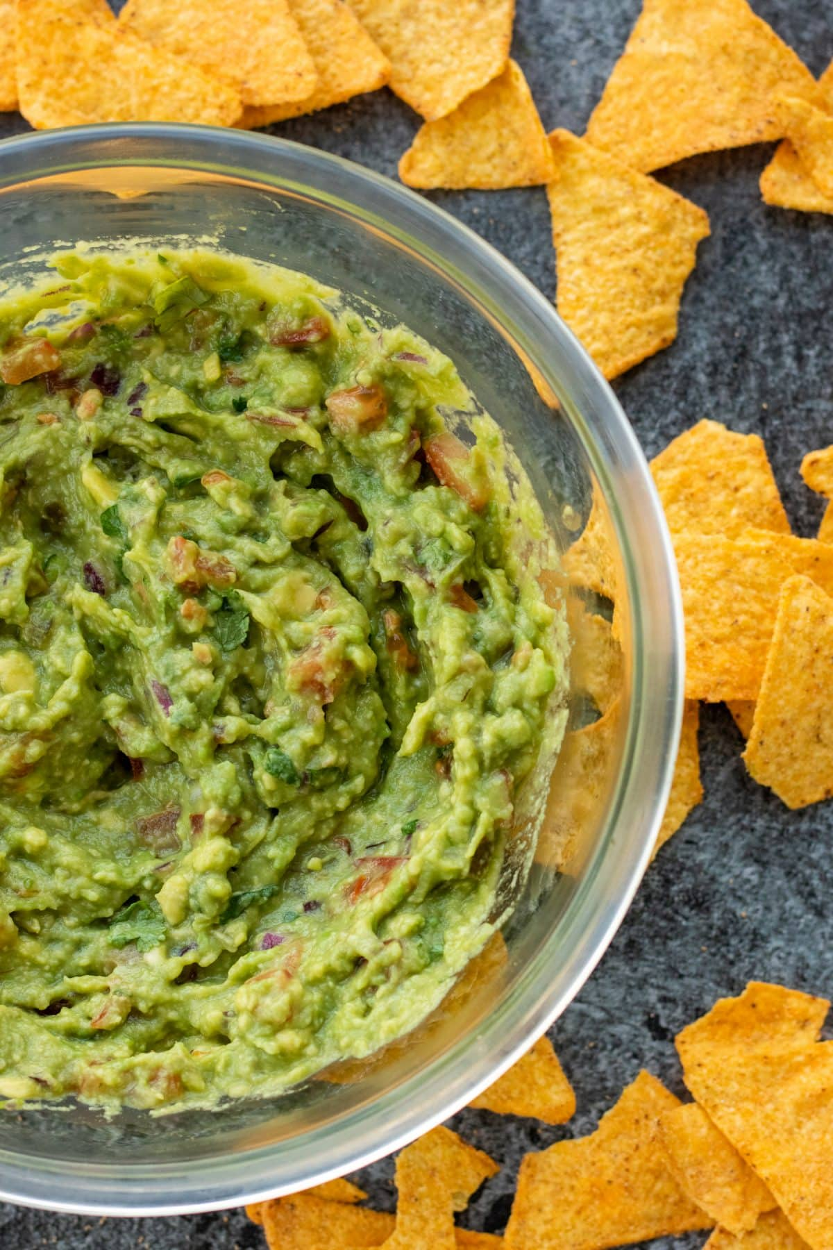top down view of a bowl of guacamole surrounded by tortilla chips