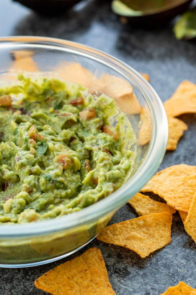 side view of a bowl of guacamole with tortilla chips on the side