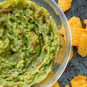 top down view of a bowl of guacamole with tortilla chips on the side