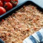 moussaka with a golden cheese crust in an oven tray, with some tomatoes in the background