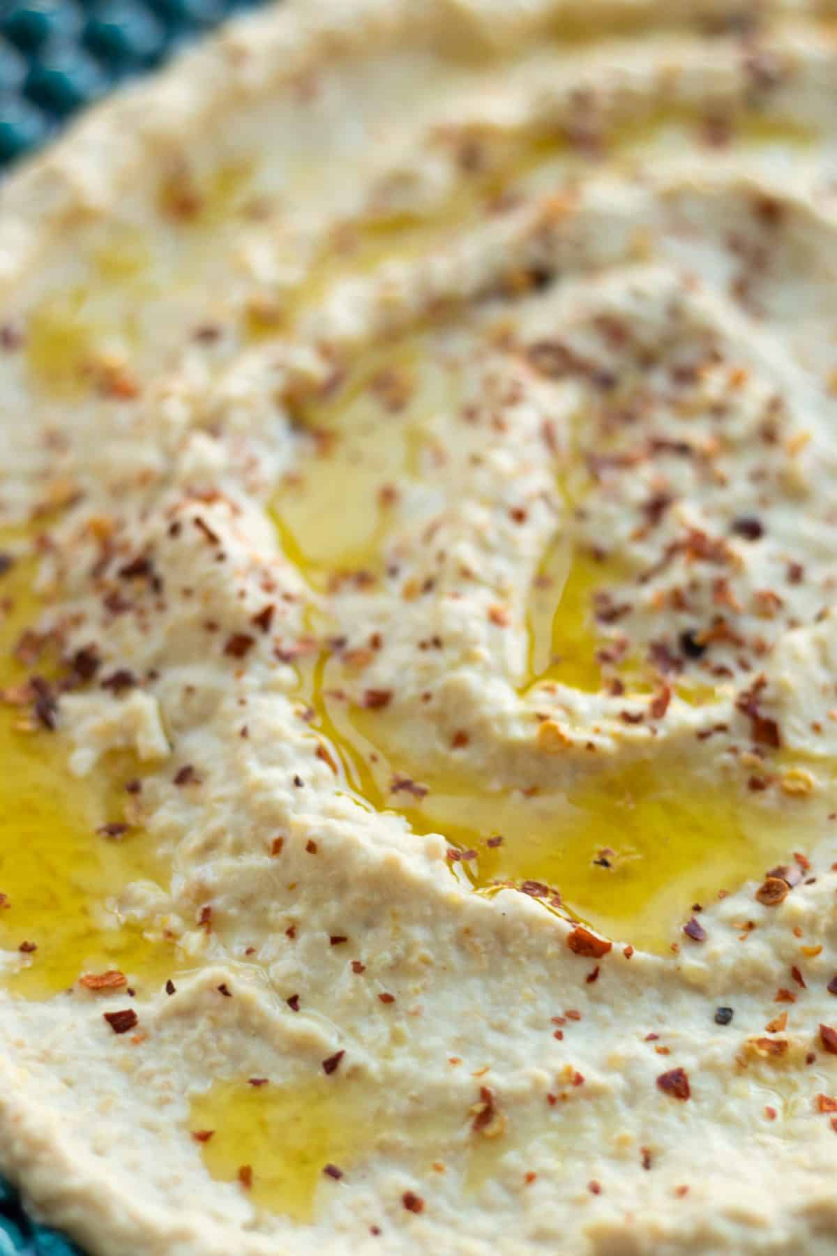 close up of hummus toppd with oliv oil and chili flakes on a blue green plate