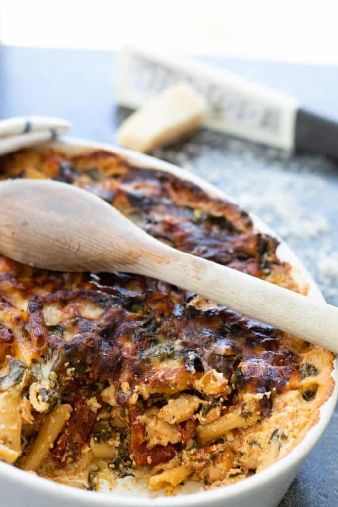 cut through view of pasta bake with spinach and sun-dried tomatoes, with a wooden spoon on top