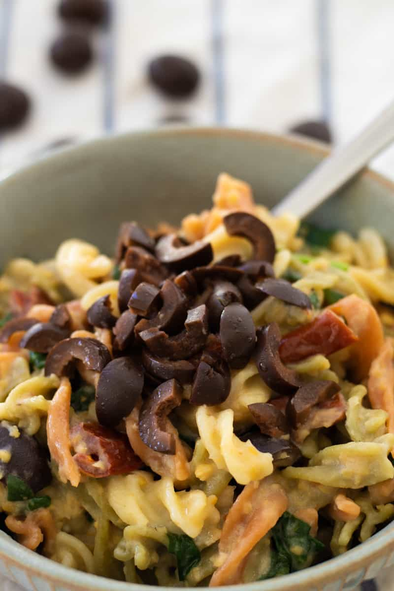 side view of a bowl of hummus pasta topped with black olives
