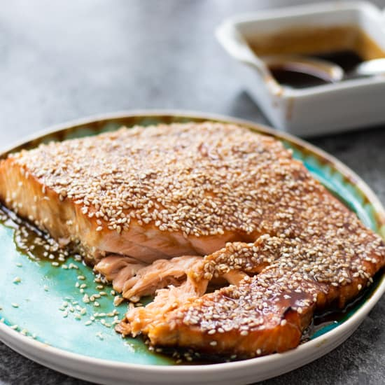 side view of baked teriyaki salmon on a turquoise plate
