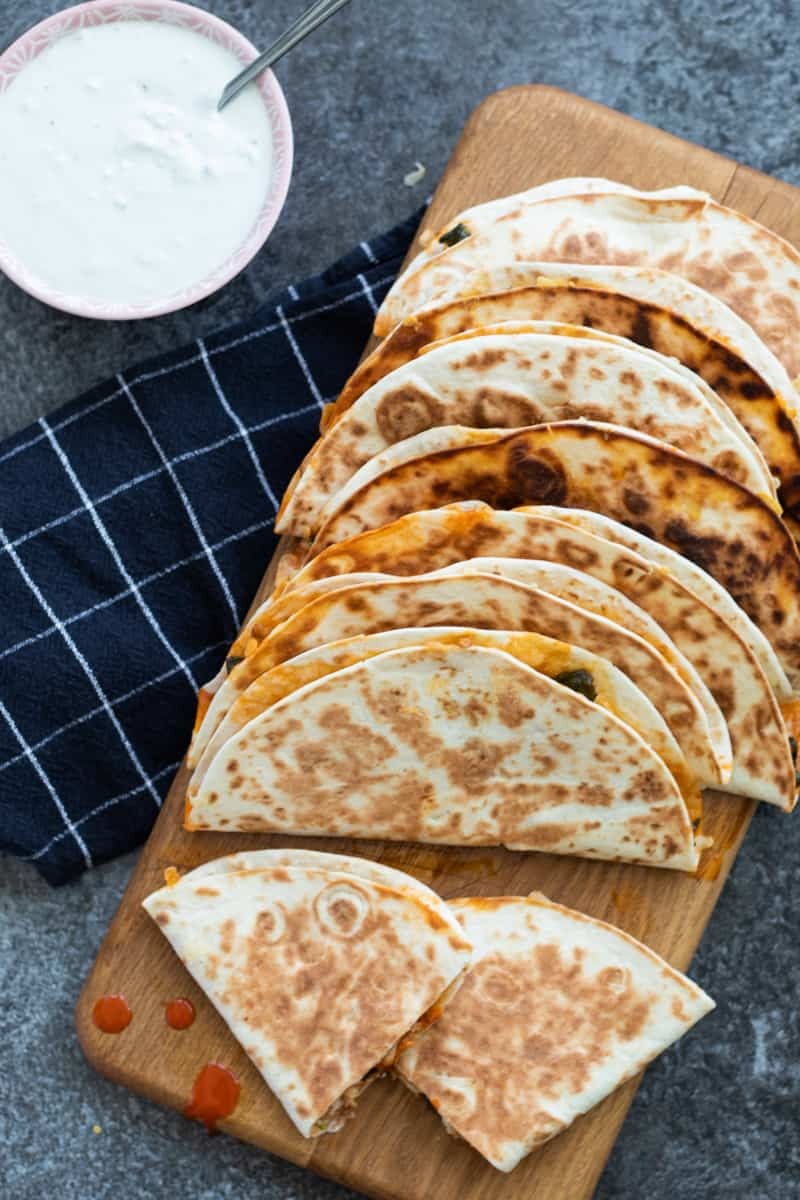 top down view of buffalo chicken quesadillas on a wooden chopping board with a bowl of blue cheese sauce next to it