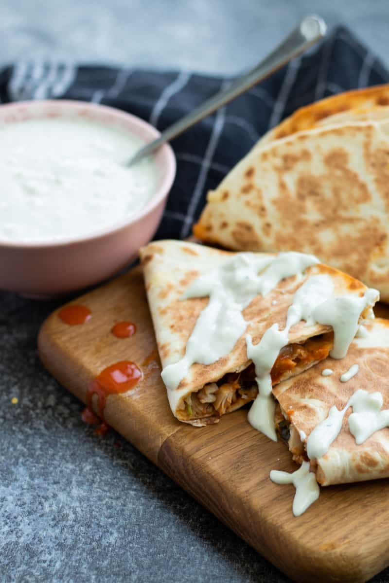 buffalo chicken quesadillas on a wooden chopping board, drizzled with blue cheese sauce and a bowl of blue cheese sauce on the side