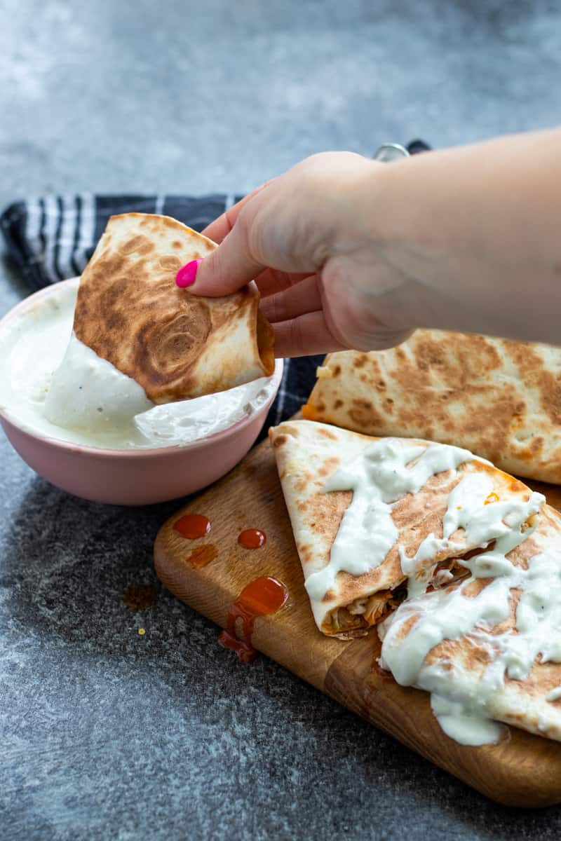a piece of buffalo chicken quesadilla being dipped into a bowl of blue cheese sauce