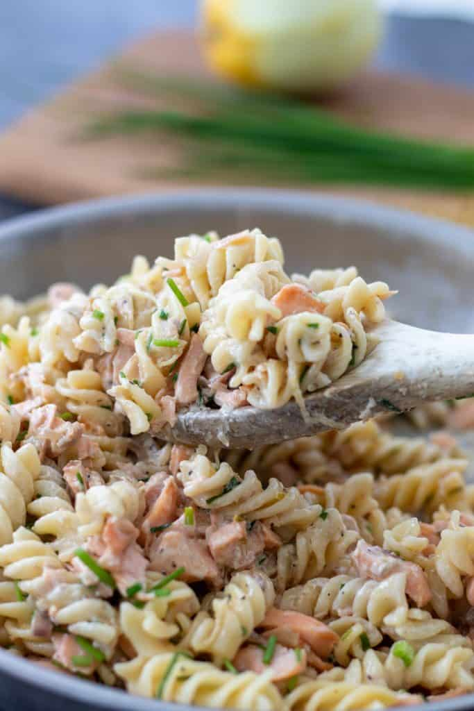a spoonful of salmon creme fraiche pasta on top of a pan full, with chives anda lemon on a chopping board in the background