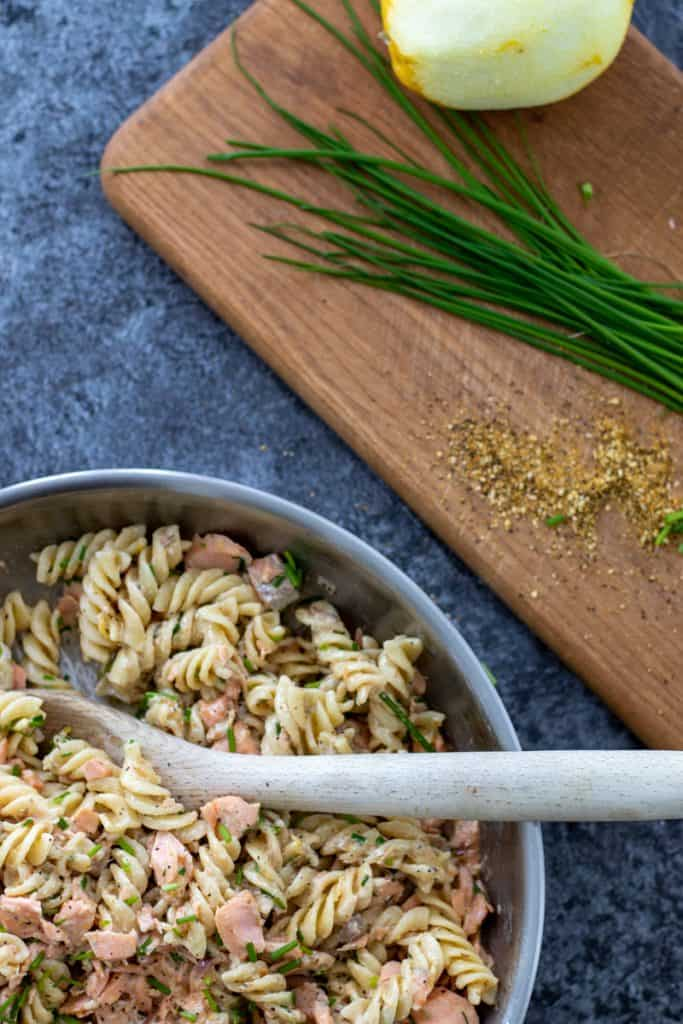 top down image of a pan full of salmon creme fraiche pasta with a wooden spoon, and a chopping board with chives, a lemon and lemon pepper next to it