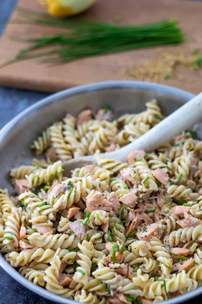 a pan full of salmon creme fraiche pasta with chives in the background