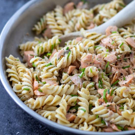 side view of a pan full of salmon creme fraiche pasta with a wooden spoon