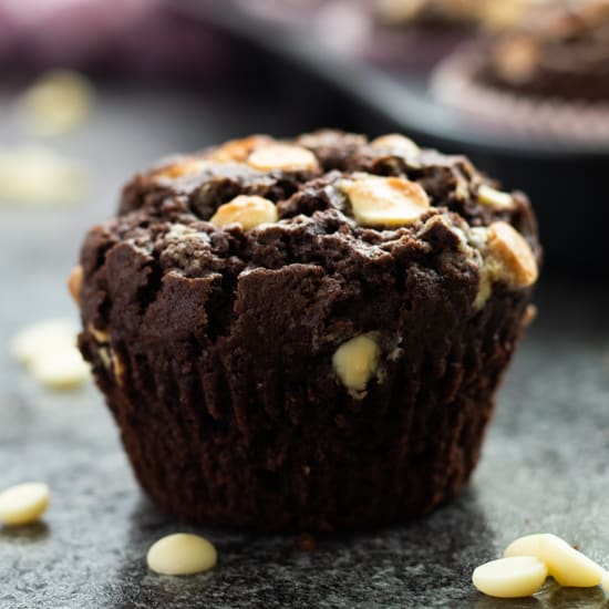 side view of a double chocolate chip muffin in front of a muffin tray full