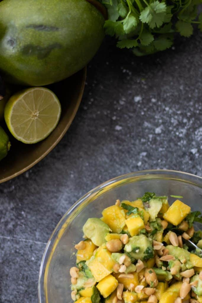 top down view of a bowl of avocado mango salad on a dark surface with salted roasted peanuts and some sea salt flakes and half a lime in the background as well as a hint of a mango and some fresh cilantro showing