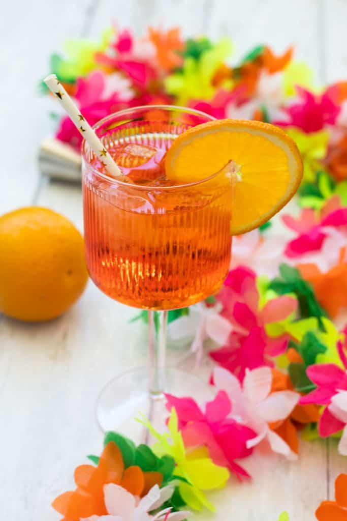 side view of an aperol spritz garnished with orange, with an orange nd some plastic flowers around it