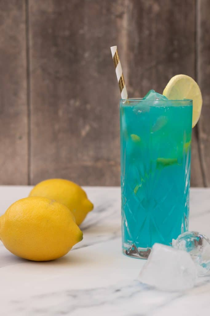 side view of a blue mocktail in a highball glass, decorated with a slice of lemon and a straw, with two lemons and some ice cubes next to it