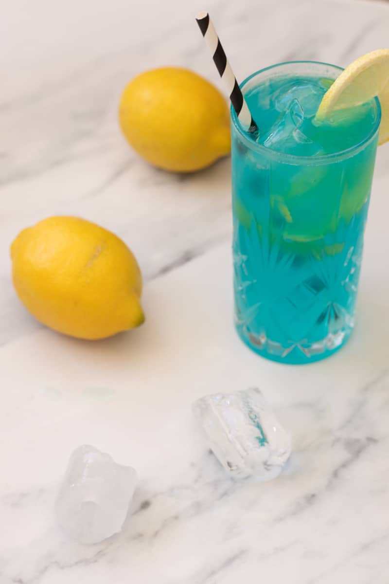side view of a blue mocktail in a highball glass, decorated with a slice of lemon and a straw, with two lemons, a tall spoon and some ice cubes next to it