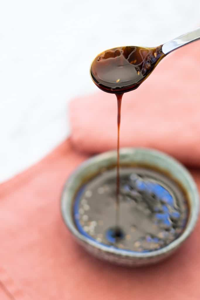 side view of a spoonful of teriyaki sauce lifted high out of a bowl full of sauce