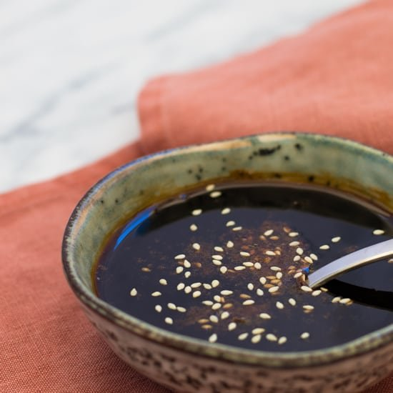 side view of a bowl of teriyaki sauce sprinkled with sesame seeds, on top of a rust colored napkin on a marble surface