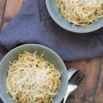 top down view of two bowls with garlic butter pasta on a wooden surface