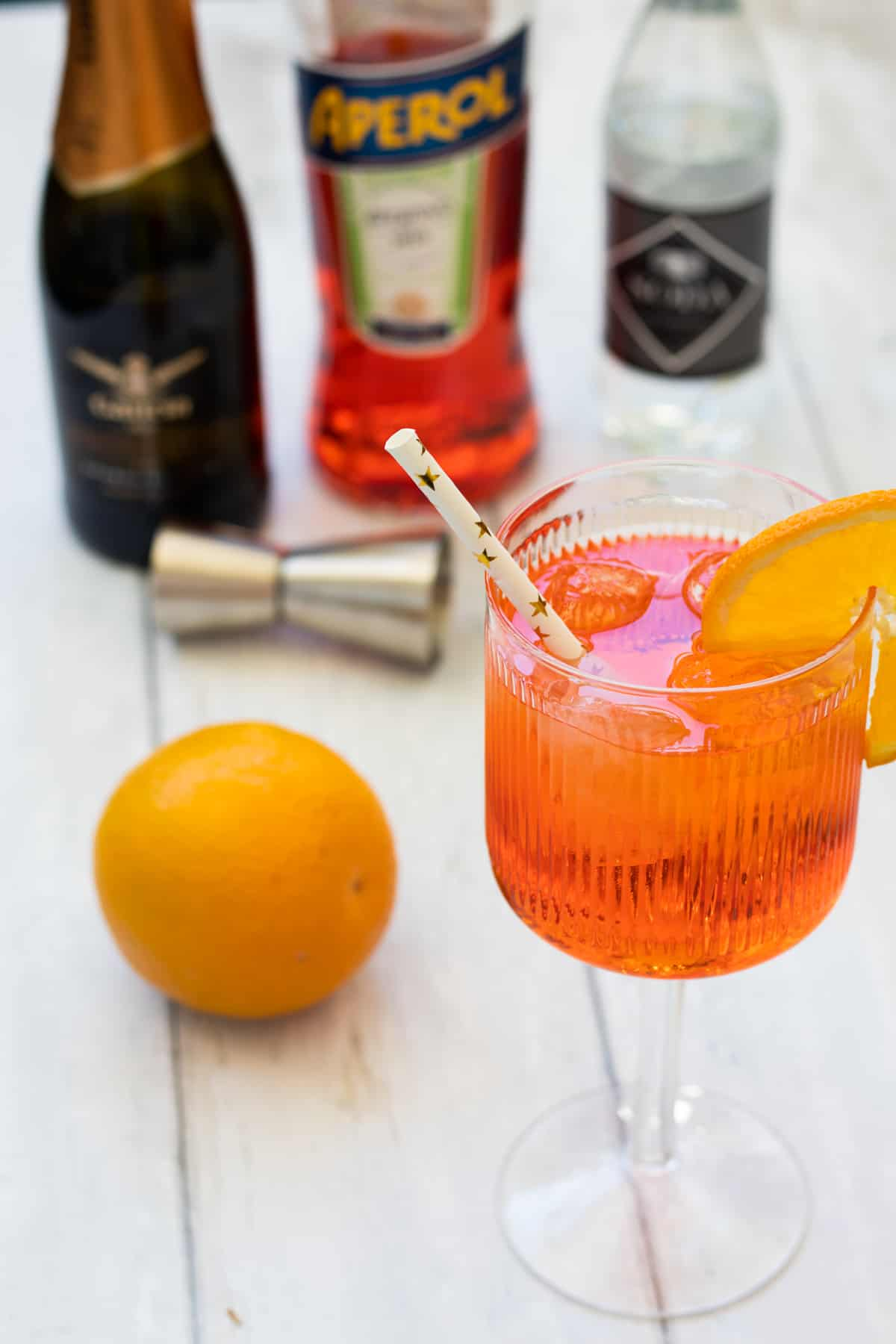 side view of an aperol spritz in front of bottles of prosecco, aperol and soda water and an orange
