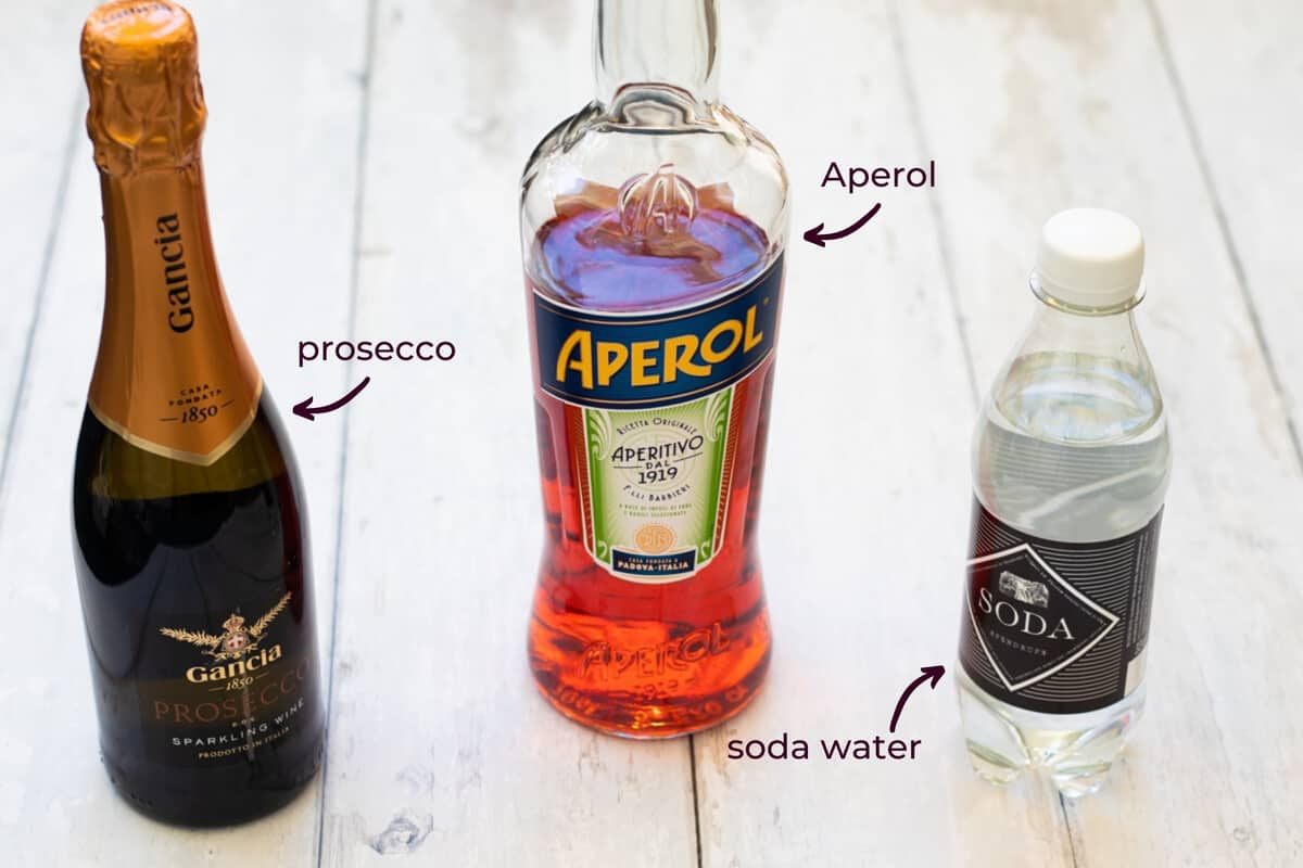 ingredients needed to make an authentic aperol spritz: prosecco, aperol and soda water