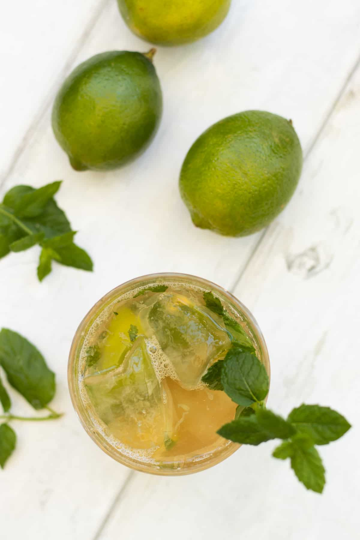 top down view of a ginger beer mocktail with limes on the side