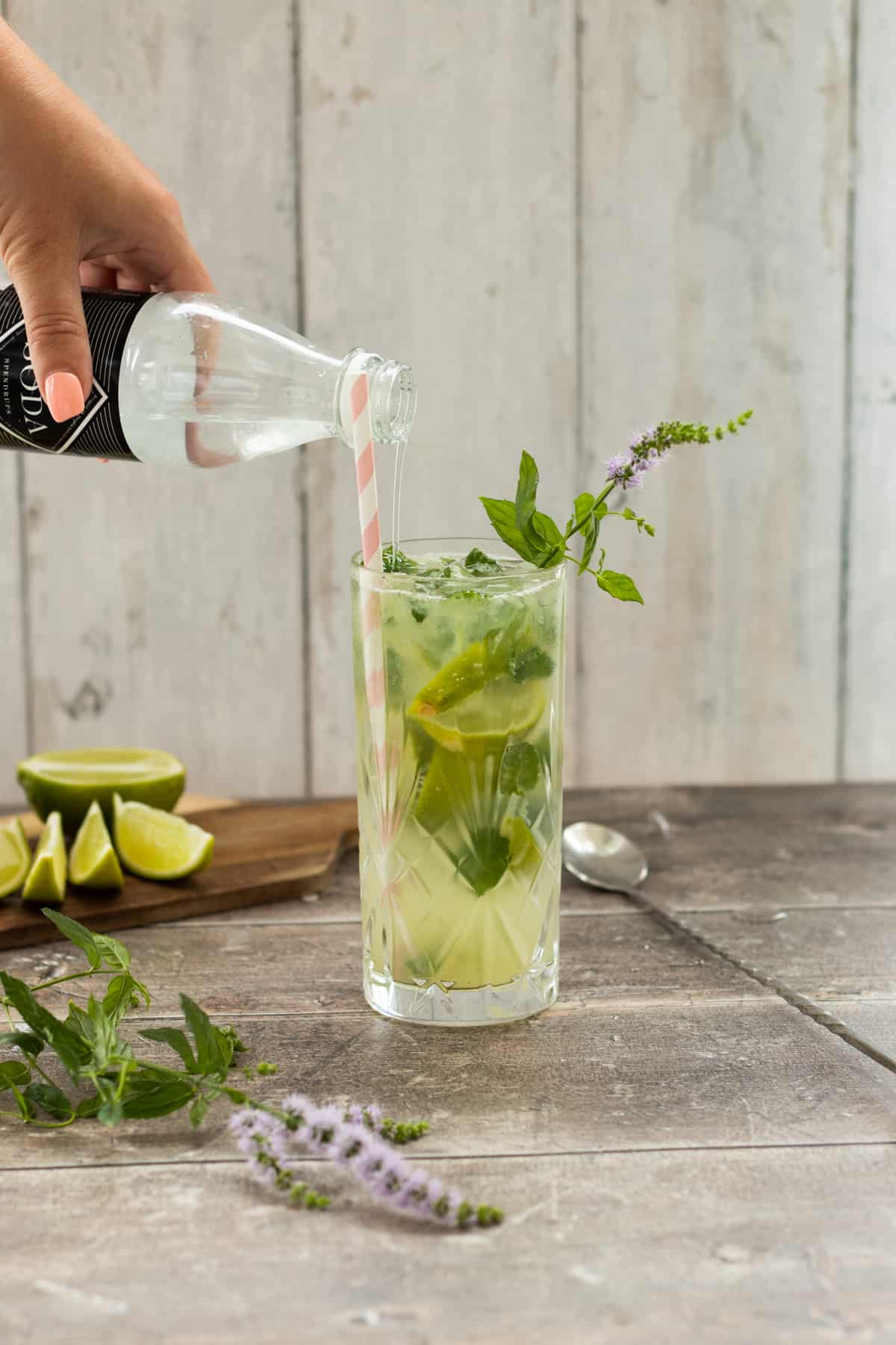 soda water being poured into a mojito mocktail