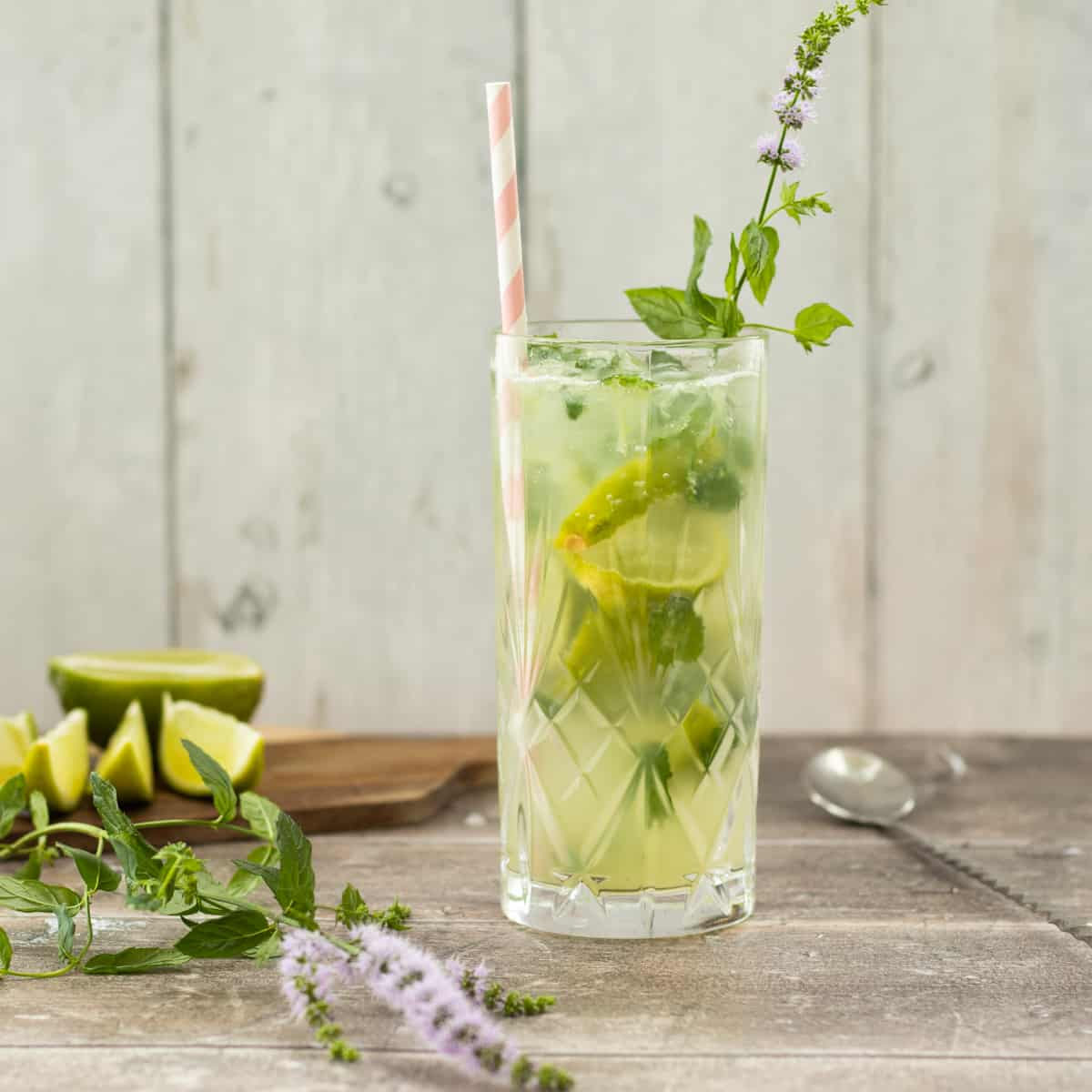 side view of a mojito mocktail with lime wedges in the background