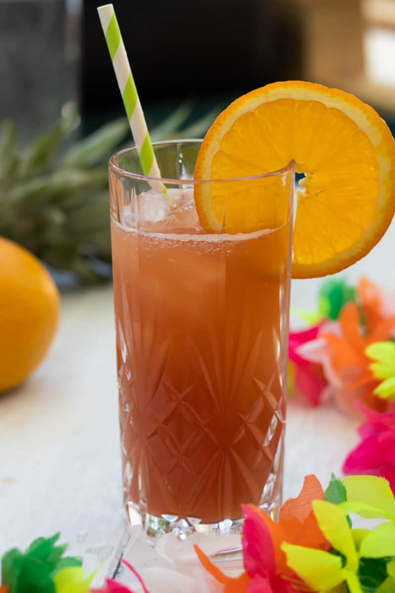 side view of a sex on the beach mocktail decorated with a slice of orange