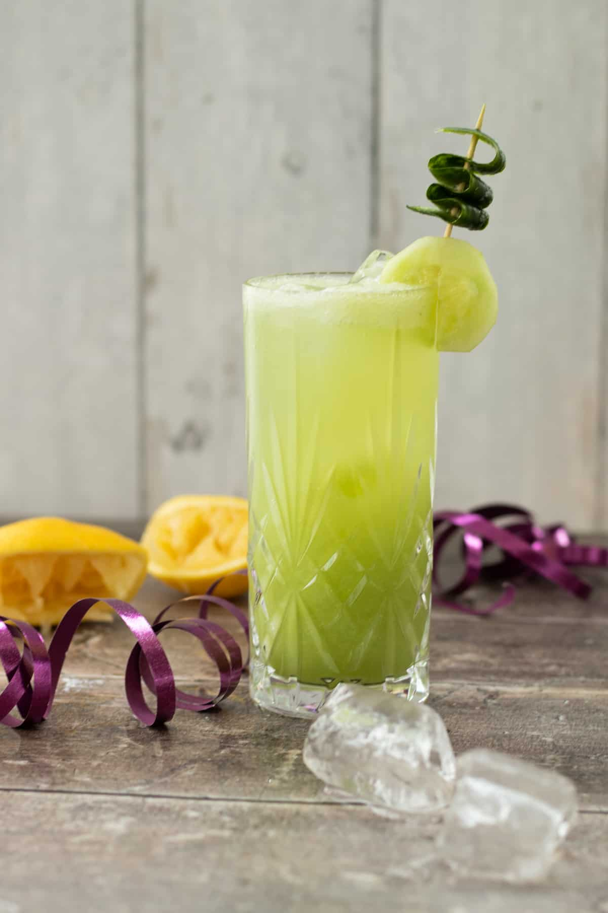 side view of a cucumber tom collins mocktail decorated with cucumber, with lemons in the background