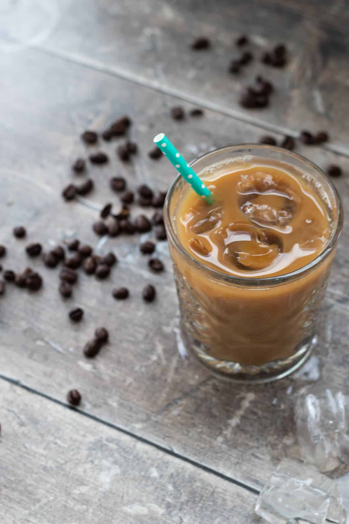 vanilla iced latte with straw on a wooden surface sprinkled with coffee beans