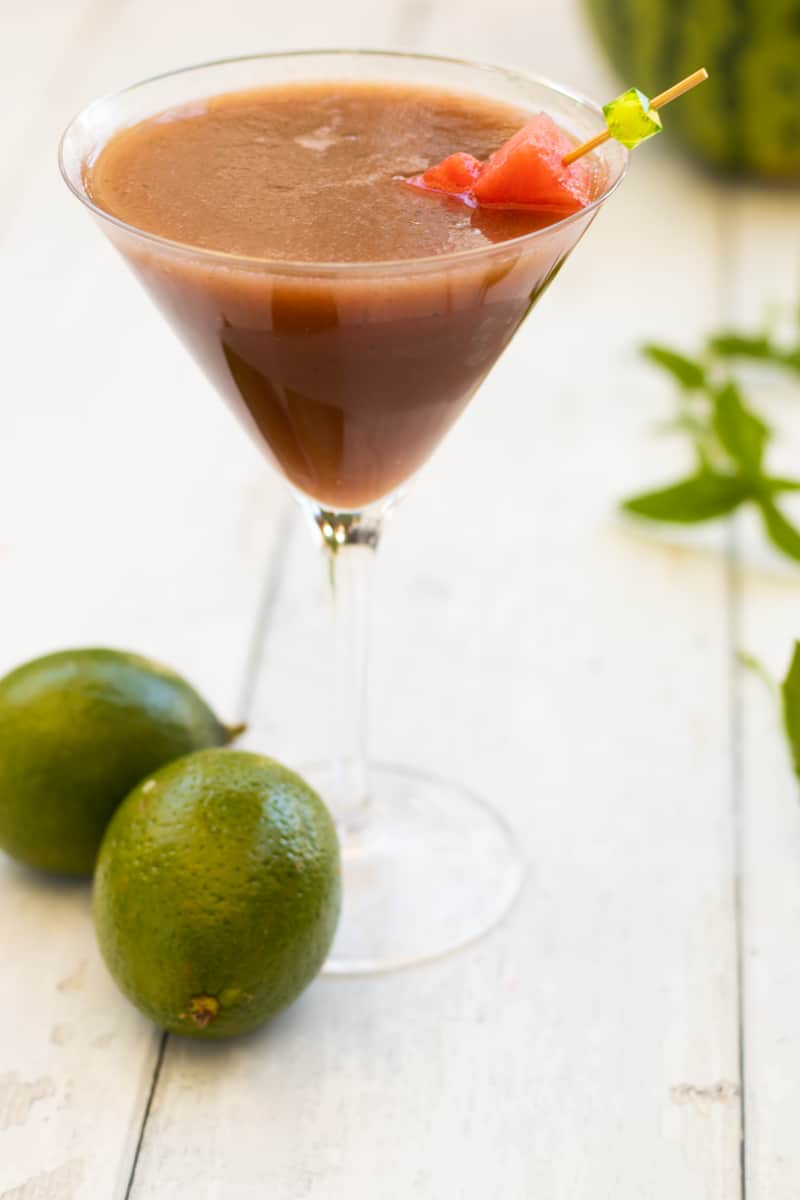 side view of a watermelon mocktail decorated with watermelon, with mint and limes in the background
