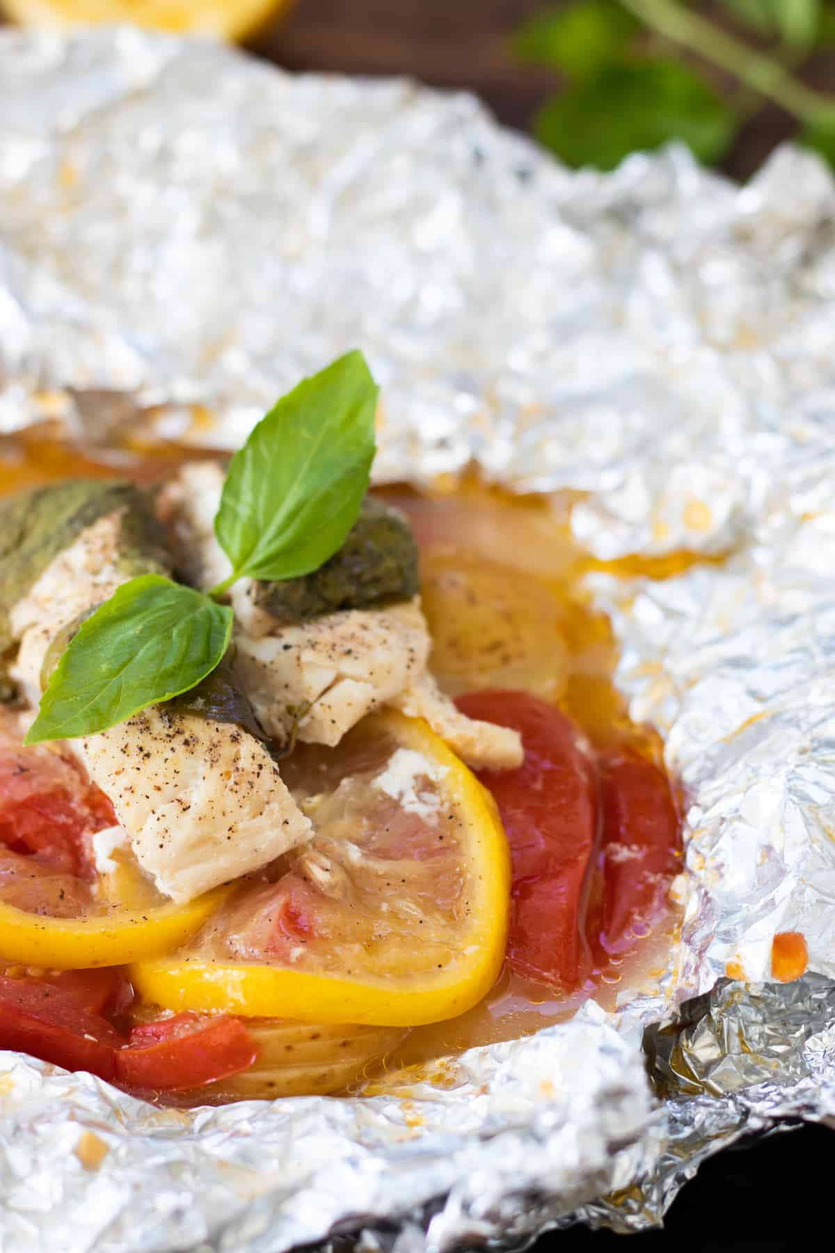 an opened foil pack after cooking, topped with basil