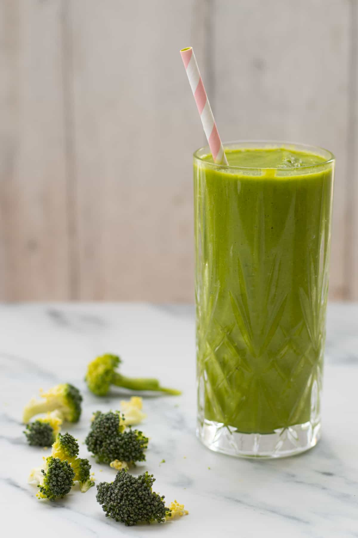 side view of a broccoli smoothie with some broccoli next to it